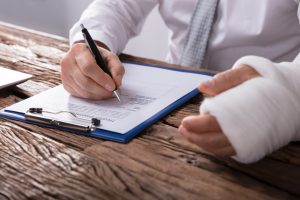 man signing a personal injury claim
